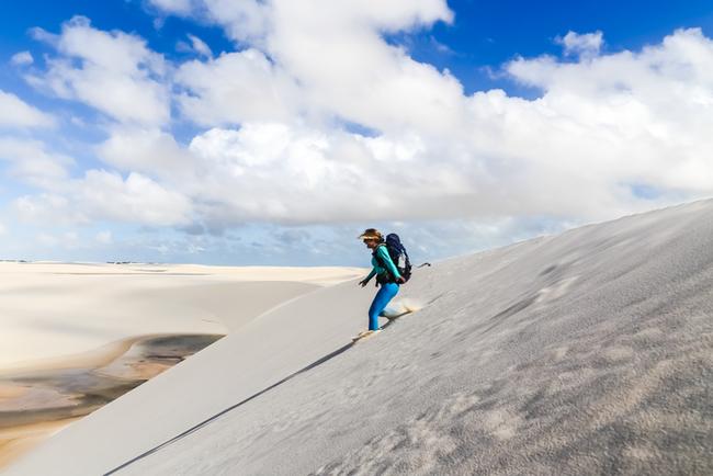 Mulher descendo as dunas no Parque Nacional dos Lençóis Maranhenses