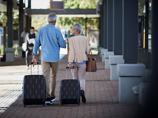foto de idosos de costas caminhando levando suas malas