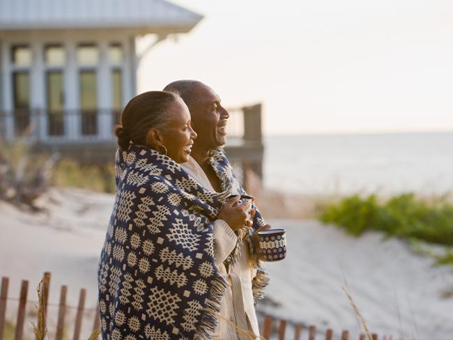 casal de idosos abraçados e enrolados em uma coberta, olhando para a direita