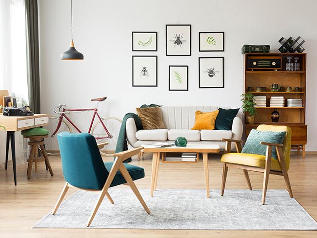 Foto de uma sala de apartamento. Em primeiro plano, duas cadeiras. Ao fundo, um sofá uma estante de madeira e uma parede branca com seis quadros.
