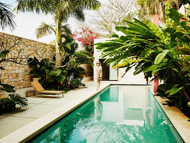 Foto de uma piscina em um ambiente que parece uma casa, cheia de árvores e plantas verdes. É possível ver um muro de pedras no lado esquredo, e ao fundo, uma mulher caminha em direção à câmera.