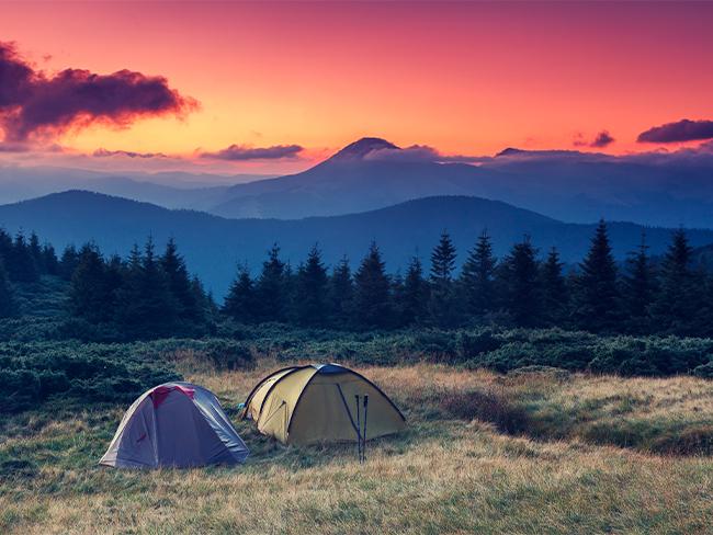 acampamento de barracas em frente a uma cadeia de montanhas