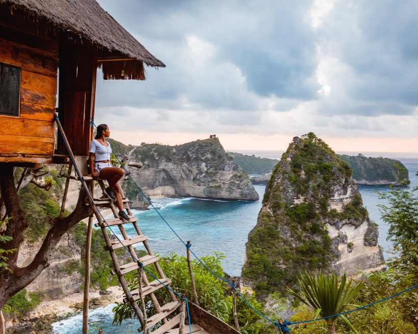 Mulher sentada em uma escada de madeira, que leva a uma casa de árvore. Ao fundo, uma paisagem cheia de montanhas e pedras gigantes na beira do mar.