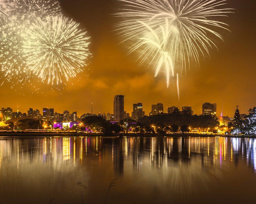 foto de uma cidade à noite, na beira de um rio, iluminada por fogos de artifício
