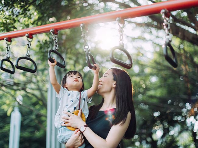 foto de uma mãe segurando o filho no colo, que está esticando os braços para se pendurar em um brinquedo de praça