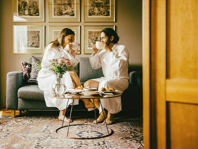 foto de um casal tomando café da manhã em um sofá de hotel