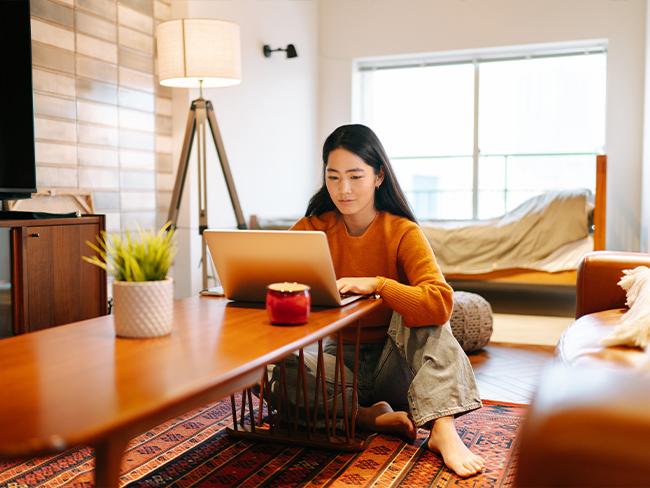 mulher usando um laptop sentada no chão no meio da casa