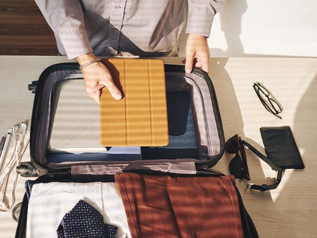 foto de cima de uma pessoa arrumando a mala de viagem